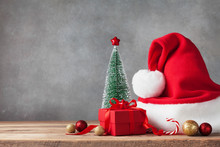 Winter Background With Christmas Gift Or Present Box, Santa Hat And Holiday Decorations. Greeting Card.