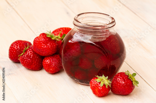Poster Fleur Strawberry jam in a jar with fresh strawberries on white wooden background. Glass jar with delicious strawberry confiture. Fresh homemade strawberry jam with berries in small jars, selective focus