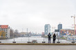 Two tourists stand at Oberbaum bridge and look at scenery of river, east side gallery and riverside Spree river with cloudy gloomy sky in winter season.