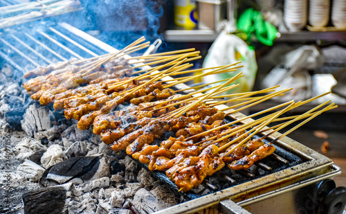 Satay skewers with chicken meat are prepared on a charcoal grill. Smoke rises from the grill.