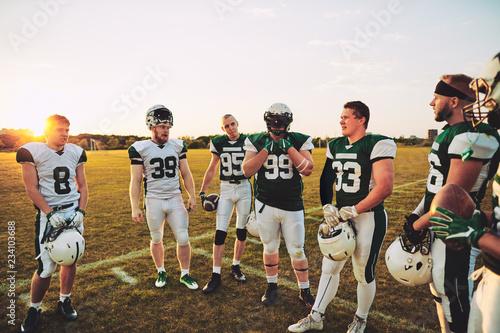 Fotografía  American football players standing on a sports field talking tog