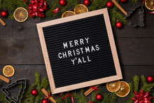 Merry  Christmas Y' All Letter Board On Dark Rustic Wood Background With Christmas Decoration And Fir Branch Frame Top View Flatlay