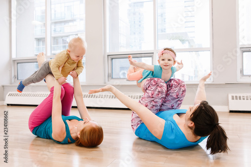 Group Of Two Young Women With Children Doing Workout In Gym Class To Loose Baby Weight Child Friendly Fitness For Mothers With Kids Lifestyle Concept Of Family Activity For Moms Buy This