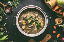 Top View Of  Beef And Cabbage Soup Or Stew In Cast Iron Cooking Pot On Dark Background With Ingredients And Wooden Spoon, Top View. Healthy Clean Low-calorie Food And Eating Concept