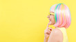 Young woman in a colorful wig with sunglasses on a yellow background