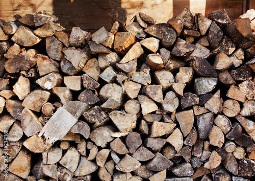 Porąbane polana drewniane na opał złożone przy ścianie stodoły szopy - Drewno na opał