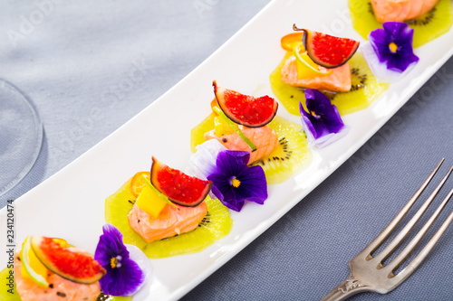 Ceviche from red trout on plate with cumquat, kiwi, figs  and flower Canvas Print