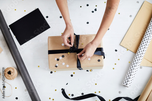 Fotografía  Directly above view of anonymous woman tying ribbon bow around wrapped gift box