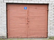 Vintage White Brick Garage With Closed Wooden Red Door With Number One