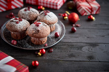 Christmas Chocolate Delicious Muffins Served On Black Ceramic Plate. Sprinkled With Powder Sugar. Cranberries On Top. Xmas Gifts And Decorations On Sides.