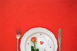 canvas print picture - Dinner on Valentine's day. Plate, Cutlery, rose and card on red background. Copy space, minimalism