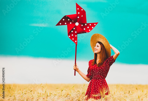 Photo a young girl is standing on a wheat field with pinwheel and waiting for rain