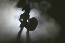 Silhouette Of Ancient Spartan Warrior With Spear And Shield In The Smoke.