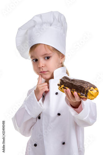 Pensive serious chef girl in a cap cook uniform, appraising the eclair Canvas Print