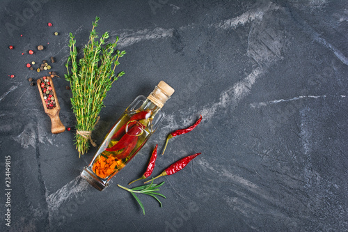 Aromatic or flavored olive oil in glass bottle with spices and herbs on black marble background