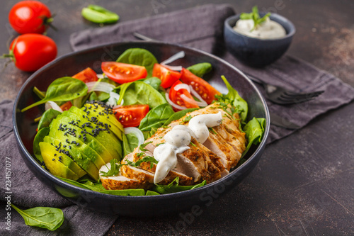 Fotografía  Chicken and avocado salad with spinach, tomatoes and Caesar dressing, dark background