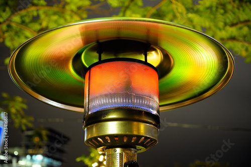 Fotografía  Close up at radiant outdoor gas heater working at night in the street restaurant
