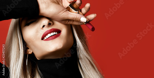 Magazine style composition woman makeup artist hold red lipstick rouge on red Fototapet