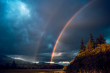 Fototapeta Rainbow - A rainbow coming down from stormy skies over the vast forests in the mountains of western Washington state USA