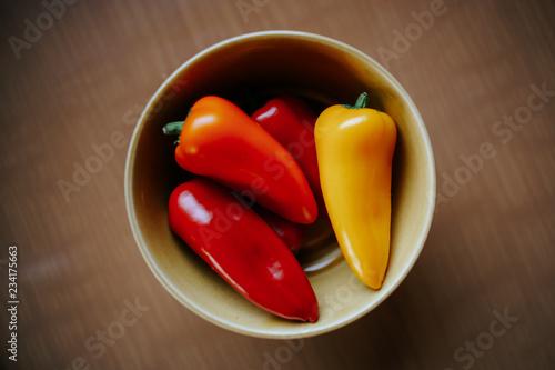 Photo  Eine Schüssel mit mehreren roten und einer gelben Paprikaschote auf einem Tisch