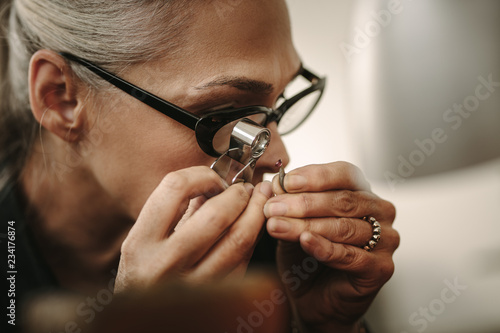 Foto Mature female jeweler looking at stone through loupe