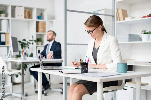 Fototapety, obrazy: Content busy attractive lady  in white jacket and eyeglasses sitting at table and making notes in diary while planning schedule in office