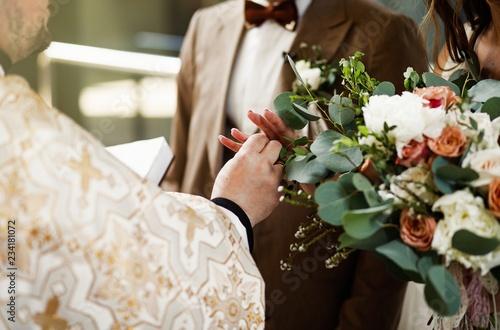 Fototapeta Bride hans with ring during orthodox church wedding ceremony. obraz