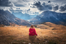 Young Woman Is Sitting On The Hill Against The Majestic Mountains At Sunset In Autumn In Dolomites, Italy. Landscape With Girl, Cloudy Sky, Orange Grass, High Rocks With Forest In Fall. Italian Alps
