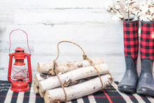 Winter Farmhouse Background With Boots, Logs And Lantern