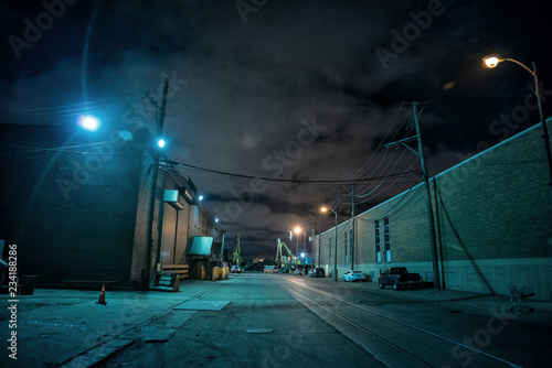 Fototapeta Industrial urban street city night scene with vintage factory warehouses and train tracks obraz