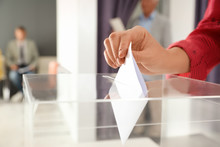Woman Putting Ballot Paper Int...