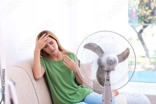 mata magnetyczna Woman suffering from heat in front of fan at home