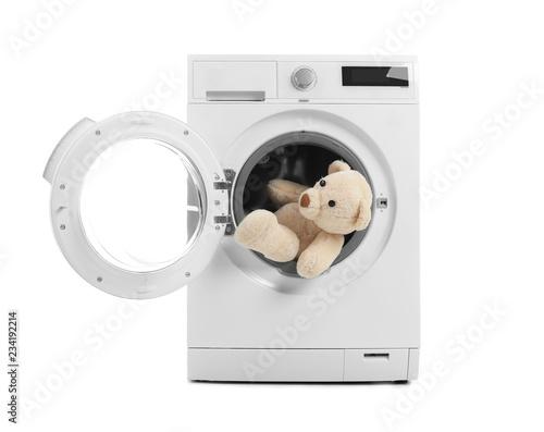 Modern washing machine with teddy bear on white background. Laundry day