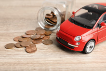 Toy Car And Money On Table. Vehicle Insurance