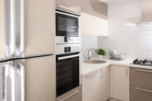Modern kitchen interior with combination oven, microwave and fridge