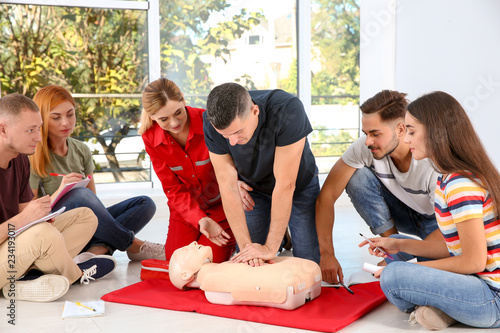 Tablou Canvas Group of people with instructor practicing CPR on mannequin at first aid class i