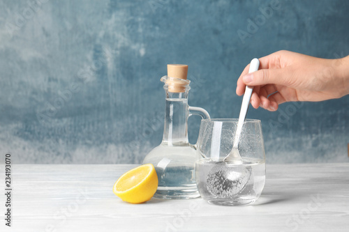 Woman mixing vinegar and baking soda in glass on table. Space for text