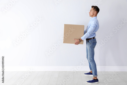Fotografía  Full length portrait of young man carrying heavy cardboard box near white wall