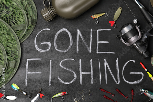 "Flat lay composition with angling equipment and words ""GONE FISHING"" on dark background"