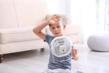Little Boy Suffering From Heat In Front Of Fan At Home