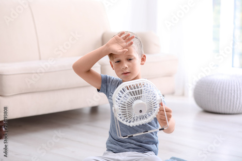 obraz PCV Little boy suffering from heat in front of fan at home