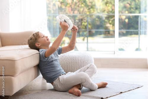Fotografia  Little boy with fan relaxing at home. Summer heat