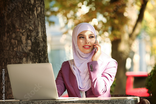Muslim woman talking on phone in outdoor cafe