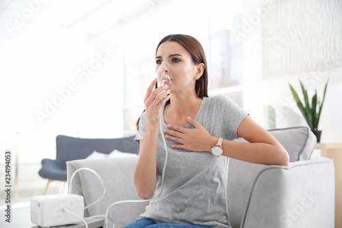 Young woman with asthma machine in light room Canvas Print