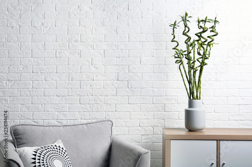 Vase with green bamboo on table in living room. Space for text