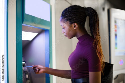 Fotografia, Obraz Woman withdrawing money from a cash machine