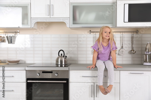 Cute little girl near oven in kitchen