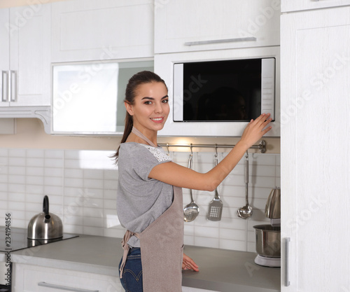 Young woman using microwave oven at home