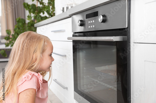 Little girl baking something in oven at home