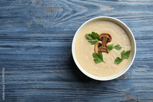 Bowl of fresh homemade mushroom soup on wooden background, top view with space for text